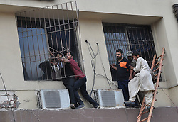 May 31, 2017 - Lahore, Punjab, Pakistan - A view of the fire erupted and citizens trying to exit a woman from the hotel,  fire erupted due to short circuit at hotel in Lahore. (Credit Image: © Rana Sajid Hussain/Pacific Press via ZUMA Wire)