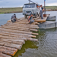 MONGOLIA. A van used by an archaeology expedition unloads from pontoon ferry across the Shishgit River north of  Tsaagan Nuur.