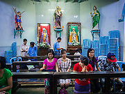 08 JUNE 2014 - YANGON, MYANMAR:  Sunday services at St. John's Catholic Church in Yangon. It was built in 1900 and was one of the first Catholic churches built in Yangon. Yangon has the highest concentration of colonial style buildings still standing in Asia. Efforts are being made to preserve the buildings but many are in poor condition and not salvageable.   PHOTO BY JACK KURTZ