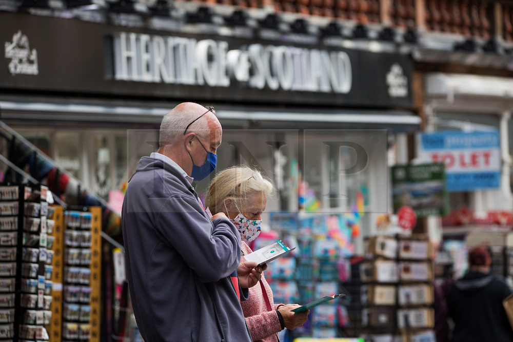 © Licensed to London News Pictures.  13/09/2021. Edinburgh, Scotland. Members of the public are seen reading a map outside souvenir shop in Edinburgh as Scotland's Covid cases tripled after return of schoolchildren. Photo credit: Marcin Nowak/LNP