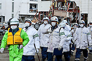 Rescue workers move through the effects of the tsunami that struck north east Japan on March 11th Kamaishi,, Iwate, Japan. March 17th 2011