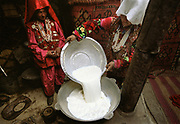 """Djer Qabtshal summer camp: two women (unmarried woman on the right - white veil called Joluk means unmarried - married woman on the left - red veil called Joluk means married) preparing """"Kurut"""": a yak cheese that is then dried on top of the yurt or else, making it hard as stone and easy to preserve through winter, when yaks do not give any milk.<br /> <br /> Adventure through the Afghan Pamir mountains, among the Afghan Kyrgyz and into Pakistan's Karakoram mountains. July/August 2005. Afghanistan / Pakistan."""