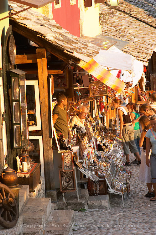 The busy old market bazaar street Kujundziluk with lots of tourist craft and art shops and street merchants. Sunset late afternoon light. Historic town of Mostar. Federation Bosne i Hercegovine. Bosnia Herzegovina, Europe.