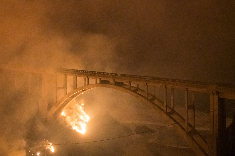 Santa Cruz County Sheriff's Deputy Ryan Farotte looks over a destroyed property on Empire Grade on Aug. 20, 2020 after it was destroyed in the CZU Lightning Complex fire near Bonny Doon, Calif.