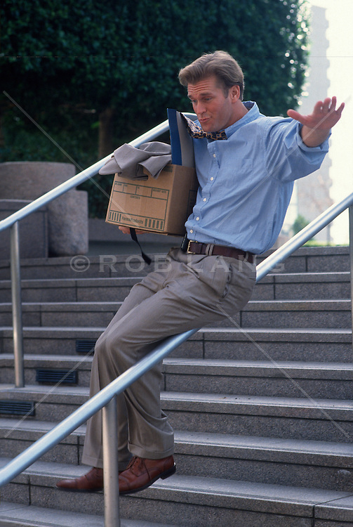 Businessman holding a box of office supplies sliding down a banister in a joyous manner