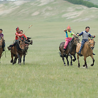 Young, costumed bareback riders approach finish line of a 20km race at a traditional naadam festival on a remote pass in Arbulag Sum, near Muren in Hovsgol Aimag, Mongolia.