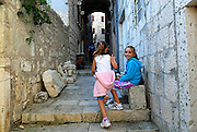 Children (5 years old, 9 years old) relaxing in paved streets of old Korcula town. Korcula old town, island of Korcula, Croatia