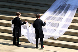 Pageboys hold the train of the dress of Meghan Markle as she arrives at St George's Chapel at Windsor Castle for her wedding to Prince Harry.