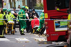 Ladbroke Grove, London, November 17th 2016. A double decker bus crashes into Kensal House on Ladbroke Grove prompting a major response from the emergency services including the air ambulance. According to Detective Chief Superintendent Ellie O'Connor of Met Police Kensington and Chelsea, 14 people including the driver were hurt, with none sustaining life-threatening or life changing injuries. Police officers would not speculate on the cause of the accident, but apologised for delays and commended all branches of the emergency services for their prompt and efficient response. The bus will be towed away for further investigations. PICTURED: A woman awaits transportation from the scene as paramedics, police and fire fighters work at the scene.