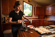 USA, Oregon, Eugene, young woman adding olive oil to the tomatoes for bruschetta. MR