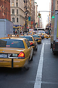 a typical New York City street filled with yellow cabs at rush hour
