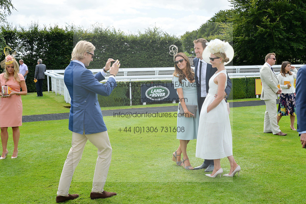 Left to right, OWAIN WALBYOFF photographing his wife NATALIE PINKHAM, WILL GREENWOOD and CAROLINE GREENWOOD at the Qatar Goodwood Festival - Ladies Day held at Goodwood Racecourse, West Sussex on 30th July 2015.