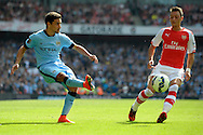 Manchester City's Jesus Navas crossing the ball past Arsenal's Mesut Ozil. Barclays Premier league match, Arsenal v Manchester city at the Emirates Stadium in London on Saturday 13th Sept 2014.<br /> pic by John Patrick Fletcher, Andrew Orchard sports photography.