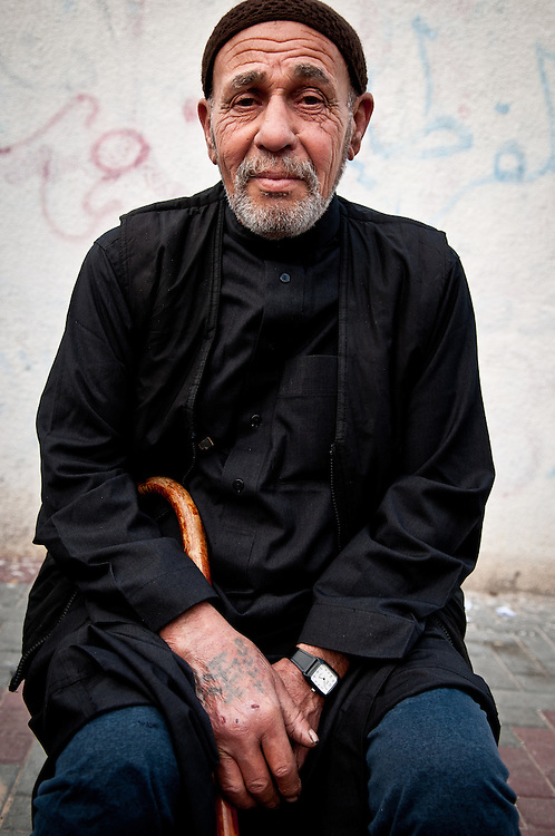 An old man poses for a portrait.