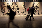 Hoarding depicting people walking by interacts with commuters passing by during rush hour during works at an underground station in London, England, United Kingdom. (photo by Mike Kemp/In Pictures via Getty Images)