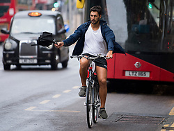 © Licensed to London News Pictures. 13/08/2020. London, UK. A cyclist makes his way through a downpour of rain on Kensington High Street, West London as the UK experiences thunderstorms and heavy rainfall following days of sunshine and high temperatures. Photo credit: Ben Cawthra/LNP