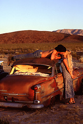 cowboy and a girl kissing around an abandoned car in the desert