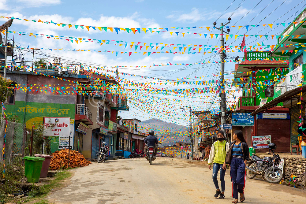 Colourful flags fill the sky along Bhotewodar Road on the 6th of March 2020 in Paudi, Sundarbazar, Lamjung District, Gandaki Pradesh, Nepal.  The town is decorated as part of the Holi celebrations, also known as Festival of Colours, is one of the most popular festivals in Nepal. It takes place on the full moon day in Nepali Fagu month (February to March in Solar Calendar) and lasts for 2 days.