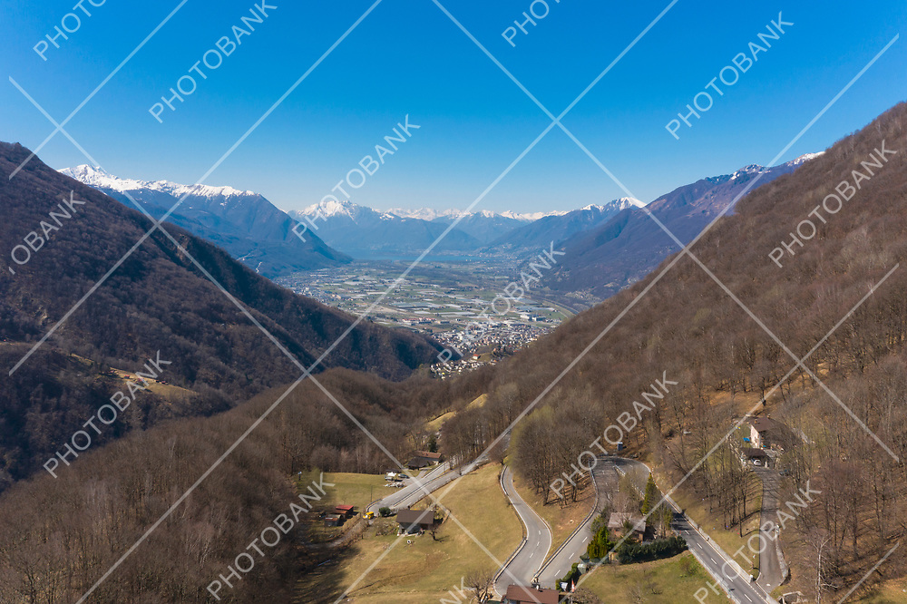 Aerial view of the Morobbia Valley, winter landscape on a sunny day with snow on the mountains. At the bottom of the valley you can see the Magadino plain and the Locarno lake