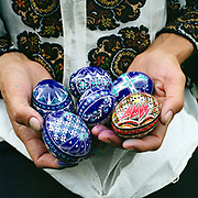 A woman holds a handful of painted eggs, Hurghis, Bucovina, Romania. In Christian Orthodox countries such as Romania there is a tradition of skilfully painting eggs before Easter. In the villages of Bucovina, the egg painters use a tool called a kishitze, a stick with an iron tip, to apply molten wax in the desired pattern to a blown egg. The egg is then dipped in the lightest colour dye to be used. The egg is then heated and the protective wax melts away and a new pattern can be added, then dipped in a different colour and so on.