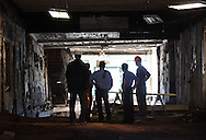 People examine the interior on the building on Broadway in Monticello that was in danger of collapsing on Wednesday, Oct. 2, 2013. The window looking out on Broadway are in the background.