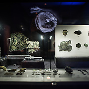One of the highlights of the National Archaeological Museum in Athens, Greece, the Antikythera Mechanism now has its own dedicated exhibit gallery in which all of its fragments are on display. Believed to date to somewhere around 100 BC to 205 BC, it was found amongst a large cache of statues, coins, and other artefacts on a sunken shipwreck discovered in 1900 by sponge divers off the coast of the Greek island of Antikythera. It was badly damaged after such a long time in the salt water, but extensive research in recent decades has resulted in a consensus that it is a kind of astronomical analog computer as well as some modern reconstructions. In the foreground are the 75 small fragments. The largest piece to the left in the back, with the circular gear clearly visible, is known as Fragment A and contains most of the Mechanism's gears.