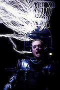 """Austin Richards of Santa Barbara, CA, is zapped by his homemade Tesla Coil. Richards wears a homemade robot outfit with a birdcage covering his head. The electrical """"lightning"""" bolts his Tesla coil zaps him with do not do any harm because he is surrounded by metal that acts a Faraday cage, harmlessly channeling the charges to the ground and protecting his body from shocks. Richards performs these stunts for trade shows and parties. Here he is doing this for a block party near Santa Barbara. California, USA"""