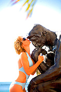 """A swimsuit-clad model kisses Rodin's """"Thinker""""  statue on Florida's luxurious Fisher island"""
