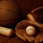 A studio shot of an American Football, a basketball and a baseball ball, mitt and bat. 17th October 2012. Photo Tim Clayton