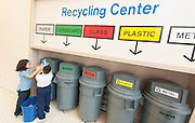 First graders Fatima Carranza, left, and Isai Rogel, right, recycle waste from their class at the Recycle Center at Lewis Elementary school, April 18, 2013.