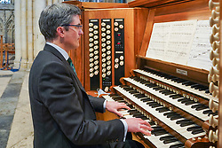 © Licensed to London News Pictures. 05/03/2021. York, UK. York Minster's Director of Music Robert Sharpe playing the Grand Organ in the cathedral's Nave at York Minister ahead of a live streamed service on Sunday 7 March. .As part of the Sunday service, the Grand Organ will be blessed and played for the first time during worship since 2018, following the completion of a once-a-century refurbishment project. Ioannis Alexopoulos/LNP