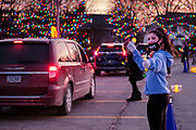 22 DECEMBER 2020 - WEST DES MOINES, IOWA: A member of the Church choir directs people into the drive through Christmas experience at Lutheran Church of Hope. About 3,000 cars per night going through the drive through Christmas pageant at Lutheran Church of Hope in West Des Moines. The church staged the drive through Christmas pageant because they decided it wasn't safe to hold in person Christmas services or pageant during the COVID-19 pandemic. On Tuesday night people started lining up to get into the pageant almost an hour before it started.     PHOTO BY JACK KURTZ