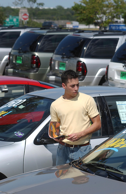 """Austin, Texas August 20, 2003:  Hispanic man (21) shops for a new car at a Chevrolet GM dealership on the """"motor mile"""" of south Austin. With the economy in the doldrums, salespeople are finding it tough to entice buyers into new vehicles this summer. MODEL RELEASED SP-39 (Hispanic man) ©Bob Daemmrich"""