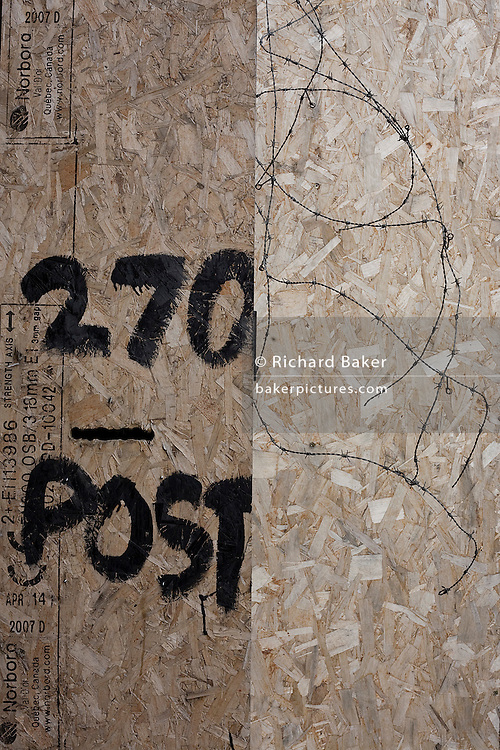 The number 270 and a slot for the post is painted on to plyboard of a business, a victim of the UK recession.