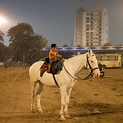 A small boy rides a horse. On the edge of the city, horses are kept under highway bridges at night while their owner sleeps nearby. The horses are used to pull horse carriage for tourists during the day.