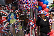 Mother and child with patriotic bunting, flags, balloons and royal memorabilia on display before the Queen's Golden Jubilee in a south London shop window. A few months before the Olympics come to London, a multi-cultural UK is gearing up for a weekend and summer of pomp and patriotic fervour as their monarch celebrates 60 years on the throne and across Britain, flags and Union Jack bunting adorn towns and villages.