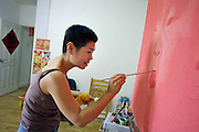 Chinese artist Yu Chen works on a painting at her Beijing apartment June 5, 2003.