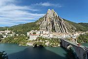 River with bridge to city at foot of sharp Rocher de la Baume mountain, Alpes-de-Haute-Provence, Sisteron, France