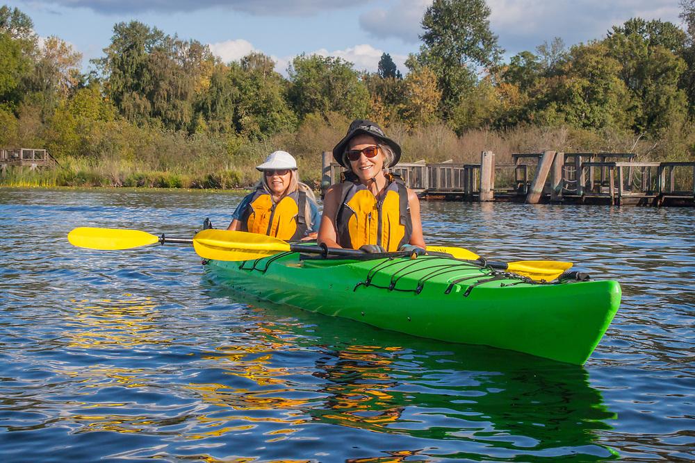 United States, Washington, Seattle. Two women paddle a two-person sea kayak on Lake Washington, near the Arboretum. MR