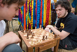 Two young men playing a game of chess outdoors at the WOMAD (World of Music; Arts and Dance) Festival in reading; 2005,