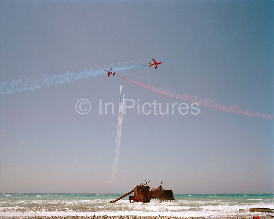 Hawk jets of the Red Arrows, Britain's RAF aerobatic team practice display using an old ship wreck as display datum (centre). Looking out to the Mediterranean Sea from the Akrotiri Peninsular, Cyprus, we see the elite team, practising their display, a show-stopping manoeuvre of their 25-minute air show display routine. A rusted and crumbling hulk of a ship lies in the shallow surf and the Hawk jets used by the Red Arrows fan out above it using red, white and blue smoke. The shipwreck's remains provide a sad foreground to the dynamic flying beyond making a graphic landscape. 'Datum' is an axis on which the Red Arrows focus their displays, from where the whole show is visible at the crowd's centre. 'The Wreck' is but one of a series of datum points selected by the team leader at short notice to simulate diverse geographical features and wind directions