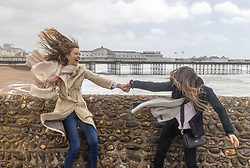 Licensed to London News Pictures. 21/05/2021. Brighton, UK. Left, Charlotte Lamb 25 and Hannah Constable from London who were meant to be holidaying in the South of France but got cancelled due to Covid restrictions enjoy the fierce winds next to Brighton Pier instead as the Met Office issue weather warnings for high wind speeds and prolonged rain today. Rain and storm winds are expected today with wind speeds in excess of 55mph along the South Coast and London as the miserable May Spring weather continues. However, sun is on the way for the May Bank Holiday with temperatures expected to hit 22c by the end of the month. Photo credit: Alex Lentati/LNP