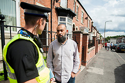 South Yorkshire Police NE Sheffield Safer Neighburhoods Team working in the Page Hall area of Sheffield PCSO Steve Shipley listens to a local resident pleased to see the police presence<br /> <br /> 15 August 2013<br /> Image © Paul David Drabble<br /> www.pauldaviddrabble.co.uk