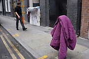 People walk past a duvet, airing on a bollard in the street in London, UK. A homeless person has made up a home in the nearby doorway.