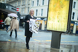 """© Licensed to London News Pictures . 01/12/2018. Manchester , UK . General Manager ANNE LATHAM (51) tears up a """" Closing Down """" sign outside her store as staff take down closing down signs from the Kendal's House of Fraser department store on Deansgate in Manchester City Centre , after a new rental agreement was secured with the landlord . Photo credit : Joel Goodman/LNP"""