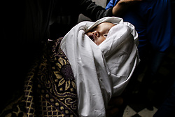 May 5, 2019 - Gaza City, Gaza Strip, 05 May 2019.  Close relatives prepare for the funeral of 14-months-old Saba Mahmoud Abu Arar, who lost her life in an Israeli airstrike that hit her home in the al-Zaytoun neighbourhood on the east of Gaza City on Saturday. Seba died immediately during the attack, while her pregnant mother was seriously wounded and died later in the evening. The airstrike took place as Israel was carrying out an intensive aerial offensive on the Gaza strip following the launching of several rockets from Gaza into Israel (Credit Image: © Ahmad Hasaballah/IMAGESLIVE via ZUMA Wire)