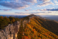 Colorful autumn foliage drapes the clifflines and valleys of North Fork Mountain in West Virginia displayed against the light of the setting sun.