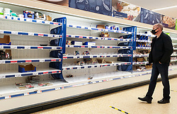 © Licensed to London News Pictures. 23/12/2020. London, UK. A shopper looks at empty shelves of meat products in Sainsbury's supermarket in north London, just two days before Christmas day. A number of supermarkets have warned that some items may run low this week. France has ended its ban on the UK arrivals and has reopened its borders with the UK under the condition of a negative COVID-19 test. It is expected that the backlog of lorries wishing to travel to Europe will take days to clear, and could impact further on food supplies. Photo credit: Dinendra Haria/LNP