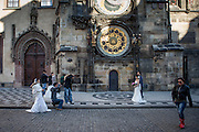A young couple from Asia getting their wedding photograph done under the Prague astronomical clock, or Prague orloj which is a medieval astronomical clock located at Old Town Square in the capital of Czech Republic.