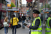 A public transport inspector is seen writing notes outside the city centre bus station in Belfast, on Monday, April 26, 2021. (Photo/ Vudi Xhymshiti)